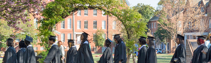 2014 graduates walking by the arch